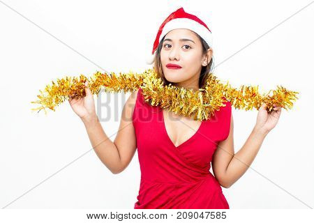 Portrait of positive young Asian woman wearing red dress and Santa hat wrapping tinsel around neck and looking at camera. Christmas and New Year concept