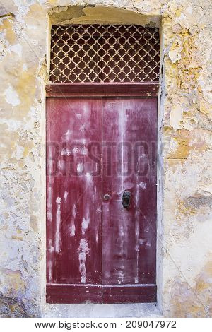 Building with traditional maltese door in historical part of Valletta. Entrance to an abandoned house on the island of Malta