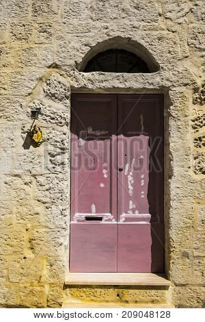 Outdoor relief of  Saint Mary Madonna with Child near the door. Entrance to a old house on the island of Malta
