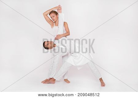Adult couple engaged in yoga. Paired training. Yoga Trainer