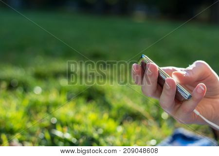 Holding An Mp3 Player In Hand In A Park