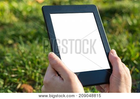 Reading An Ebook On A Tablet In The Park