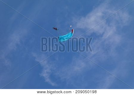Two Parachutists fly to the sky. Two tandems with parachutists in the air. Skydivers in the sky