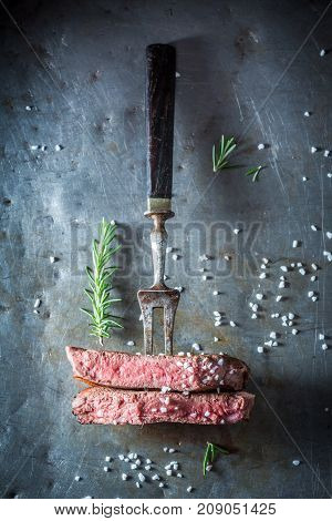 Delicious Medium Rare Steak With Rosemary On Metal Table