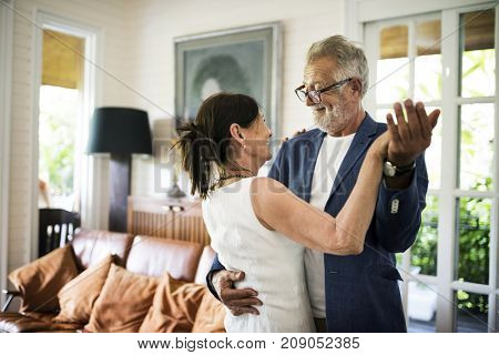 An elderly couple is dancing together