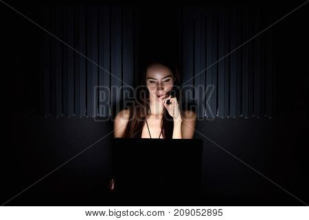 Attractive girl look at notebook in the room darkness smile