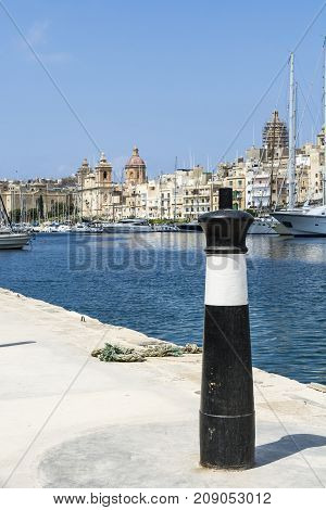 Yachts docked at the port of Malta. Boats moored in a row on the background of old city. Mooring bollard on the harbor pier against coastal Three Cities