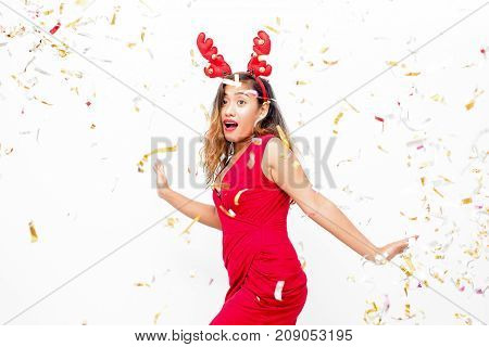 Amazed attractive lady having fun at Christmas party and dancing under confetti. Emotional surprised young woman in red dress wearing reindeer antler headband. Celebration concept