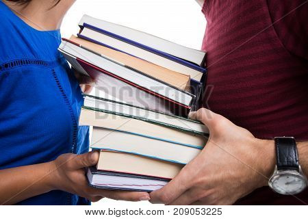 Close-up Of Students Holding Pile Of Books