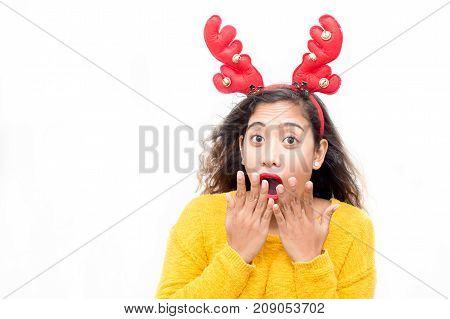 Astonished expressing woman shocked with sales and covering open mouth. Amazed young lady in deer costume looking at camera and thinking of Christmas time. Advertisement concept