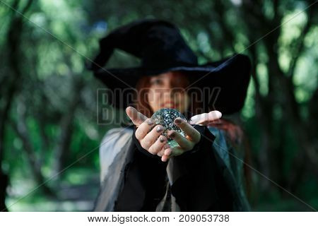 Witch holding magic ball in palms