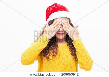 Attractive young woman in santa hat covering eyes with hands in anticipation of Christmas gift. Calm girl thinking of Christmas. New Year concept