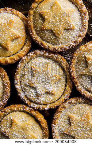 Traditional British Christmas Pastry Dessert Home Baked Mince Pies with Apple Raisins Nuts Filling Golden Shortcrust Powdered Pattern Top View Festive Atmosphere