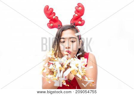 Concentrated young woman in costume playing with confetti and blowing out them. Excited beautiful lady making wish before Christmas or having fun at party. New Year concept