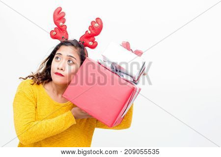Curious pretty woman shaking gifts trying to guess what is inside Christmas presents. Concentrated girl in reindeer antler headband listening to noise. New year concept