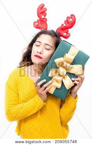 Dreamy attractive woman embracing Christmas gift and thinking what is inside present. Serene beautiful lay with closed eyes in anticipation of cool gift. New Year concept