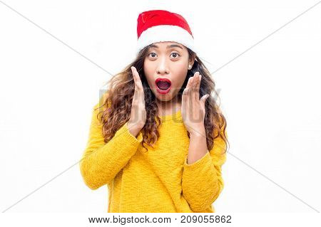 Funny shocked young woman with open mouth looking at camera. Emotional girl in Santa hat surprised with Christmas sales. Christmas shopping concept