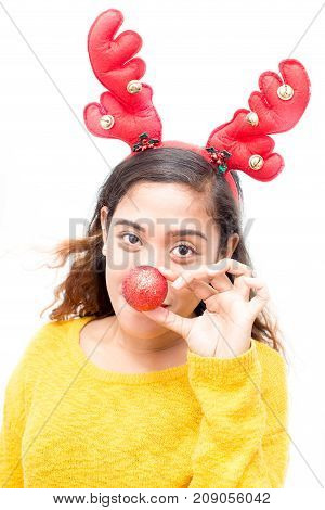 Funny young woman holding red ball near nose and looking at camera. Pleased attractive girl in good mood. Playful woman wearing reindeer antler headband. New Years costume concept