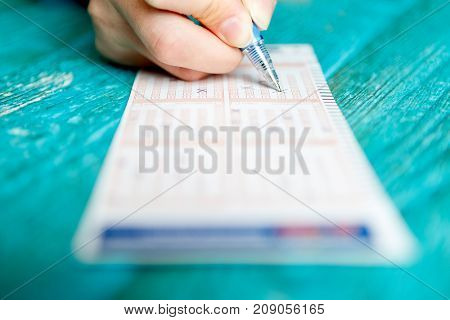 Image of man's hand with pen and lottery ticket