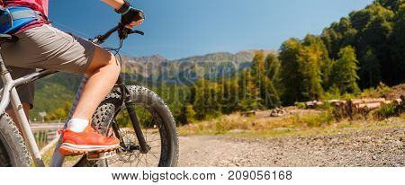 Image of girl in sneakers on bicycle