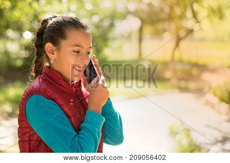 Beautiful girl talking on a smartphone in  red vest on the outdoor.Handsome smiling girl with mobile phone walking on outdoor. Portrait smiles girl. copy space. The girl with a smartphone in the hands