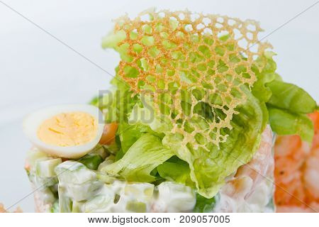 Cheese netting decoration of green salad on white background