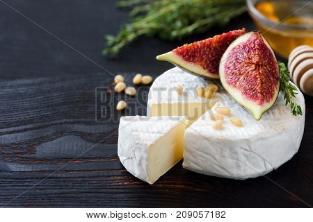 White cheese brie or camambert. Gourmet appetizer cheese plate with white cheese, figs, thyme, honey and nuts
