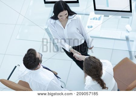 handshake manager and employee near the workplace
