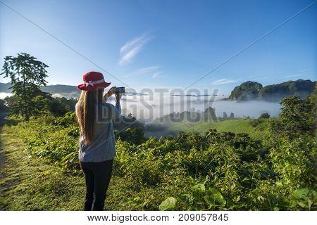 Traveler woman wearing hat using smart phone take beautiful mountain landscape shots with sea of mist .