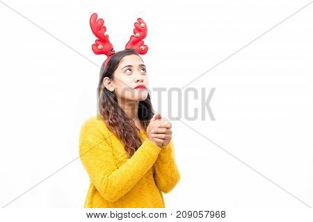 Serious pretty girl looking up while praying about miracle at Christmas. Concentrated young woman in reindeer antler headband joining hands while talking to God. Christmas wish concept