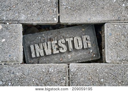 Word Investor written over a broken brick on the pavement