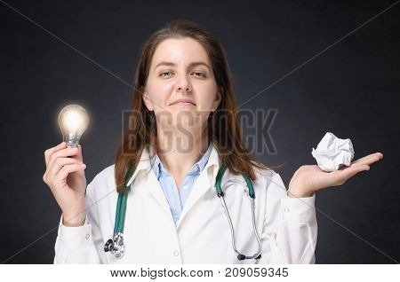 Female doctor holding a glowing light bulb and a crumpled paper ball