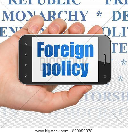 Political concept: Hand Holding Smartphone with  blue text Foreign Policy on display,  Tag Cloud background, 3D rendering