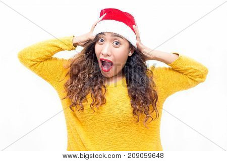 Thrilled pretty woman excited about Christmas sale and screaming while looking at camera. Worried expressing girl clutching head before Christmas. Astonishment concept