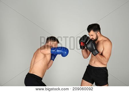 Male boxers fighting on light background