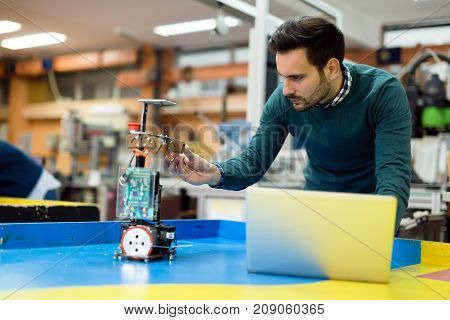Young handsome engineer testing his robot in workshop