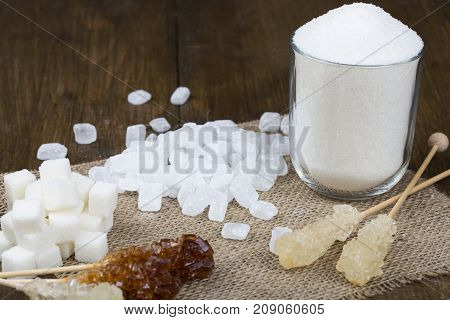 Different types of sugar on a brown wooden table. Sugar with sand in a glass. Sugar in cubes. Sugar on a stick in the form of candy. Sugar on the structural fabric.
