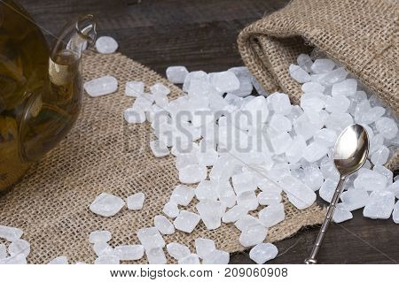 The candy sugar scattered from the bag. Sugar in a bag on a wooden surface. Sugar with a glass teapot of brewed green tea.
