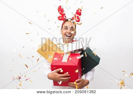 Closeup portrait of cheerful middle-aged handsome man wearing toy reindeer horns, looking at camera and holding four gift boxes. Isolated front view on white background.
