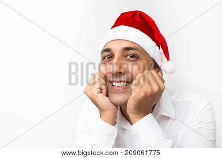 Closeup portrait of smiling middle-aged handsome man wearing Santa Claus hat, leaning on hands and looking at camera. Isolated view on white background.