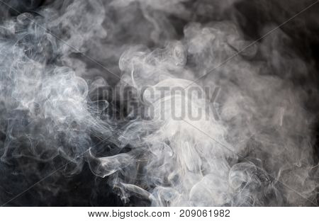 The abstract figure of the smoke on a black background .