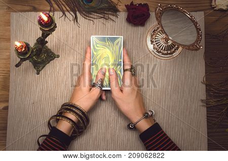 Fortune teller holding in hands a deck of Tarot cards.
