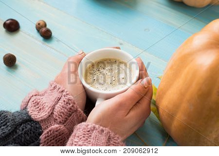 Woman's hands in sweater holding cup of coffee on the blue wooden table. Holiday concept. Girl holding a coffee cup on a wooden vintage background - winter time concept. Coffee cup