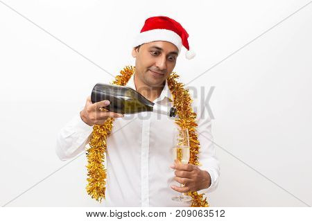 Closeup portrait of funny middle-aged handsome man wearing Santa Claus hat, tinsel and pouring champagne into flute from bottle. Isolated front view on white background.
