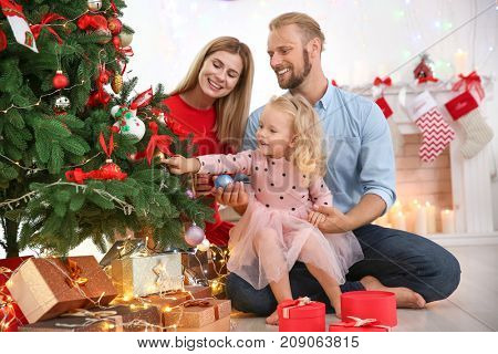 Happy couple with little daughter decorating Christmas tree at home