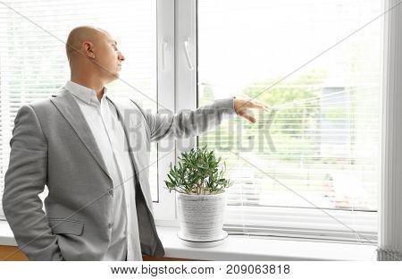 Bald man in jacket standing near window indoors