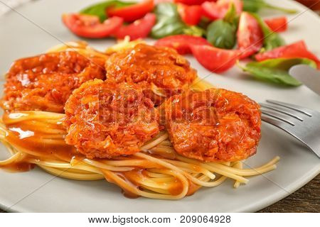 Plate with tasty sausage balls and garnish, closeup