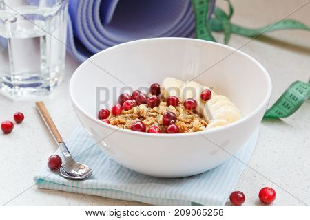 After yoga breakfast: muesli with berries and banana. Nutrition at weight loss healthy detox snack concept.