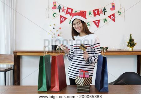 Shopping online concept. Young asian woman holding digital tablet and credit card with many christmas gift box and shopping bags.