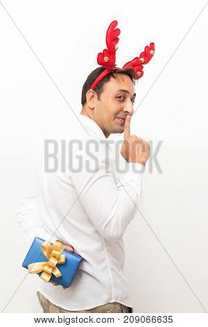 Closeup portrait of content middle-aged handsome man wearing toy reindeer horns, turning to camera, showing silence gesture and hiding gift box behind back. Isolated back view on white background.